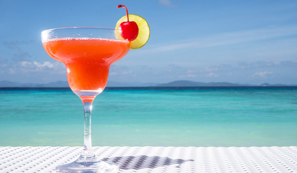 Pink drink in a cocktail glass sitting on a table overlooking the ocean
