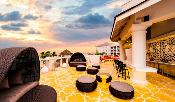 Rooftop lounge with Moroccan-inspired decor at sunset
