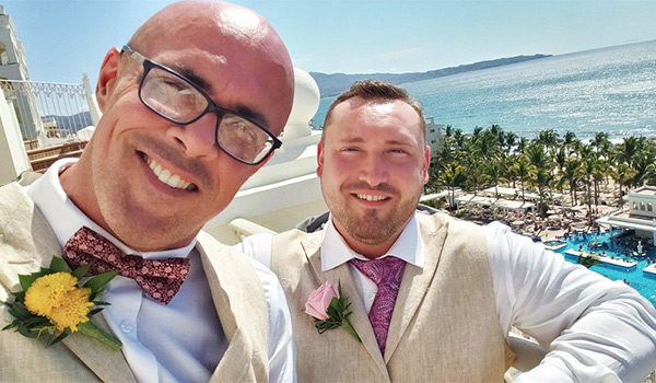 Two grooms standing on a balcony overlooking the ocean