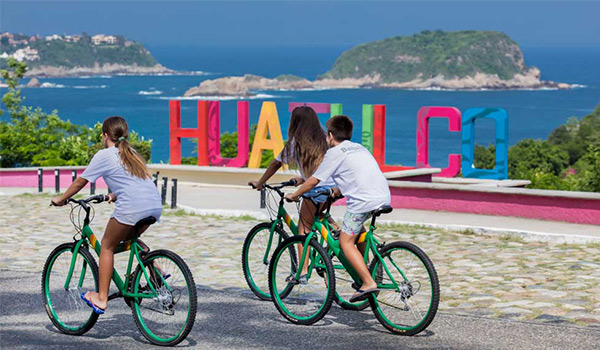 Three people riding bikes past a colourful Huatulco sign overlooking the coast