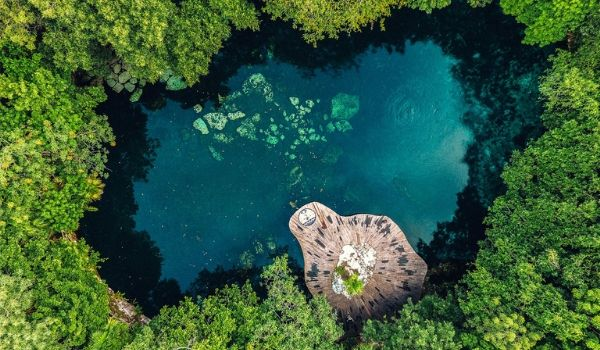 Aerial view of beautiful cenote surrounded by jungle