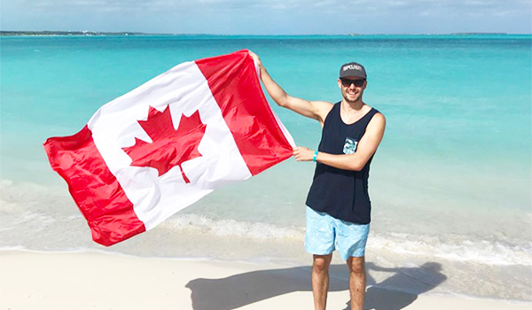 Man standing on the beach holding a Canadian flag