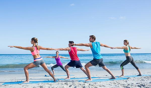 Groupe de personnes faisant du yoga sur la plage