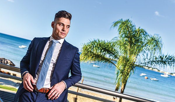 Groom posing on a hotel balcony with the ocean in the background