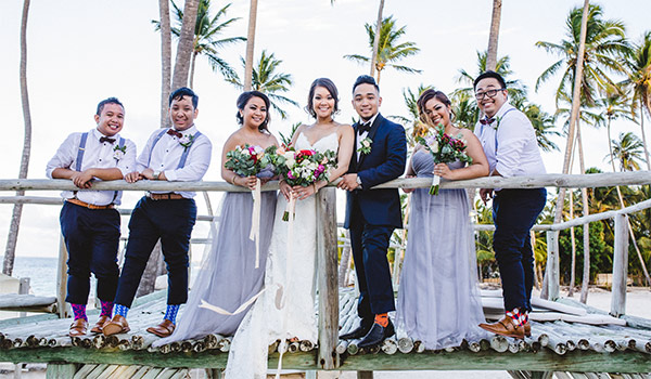 Groom and bride standing with their bridesmaids and groomsmen on a bridge by the beach