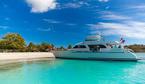 Luxuriante île isolée entourée de voiliers et de récifs coralliens