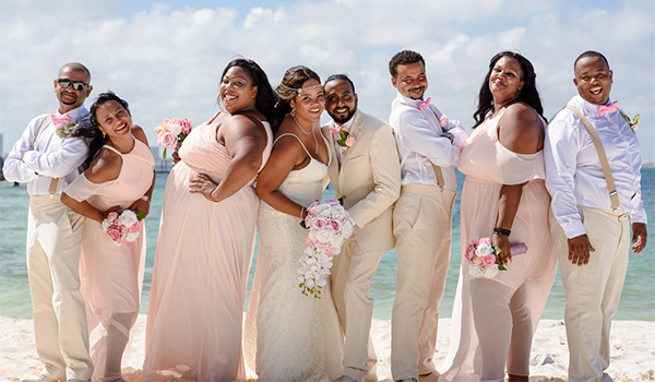 Sheniqua and Ejaz posing with their wedding party on the beach