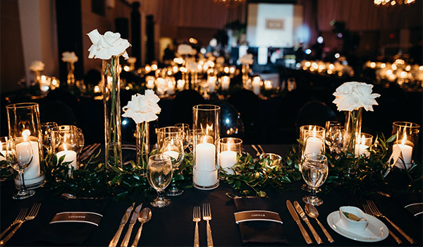 Dinner table with glamorous candles and white floral arrangements