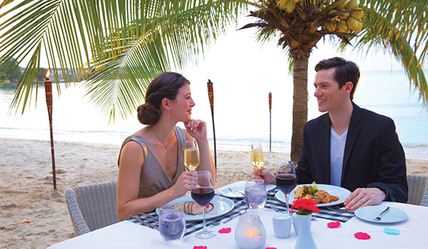 Couple enjoying a romantic dinner on the beach underneath a palm tree