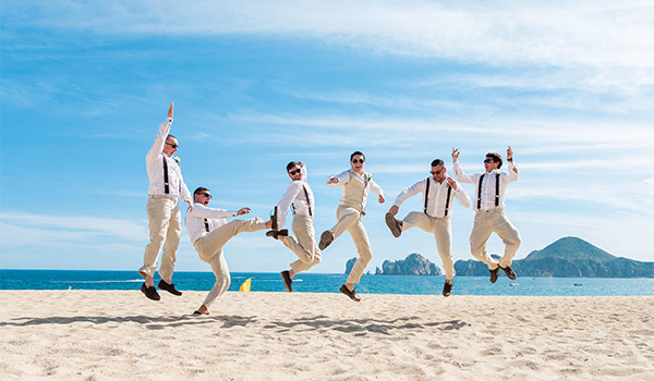 Groomsmen jumping in the air on the beach