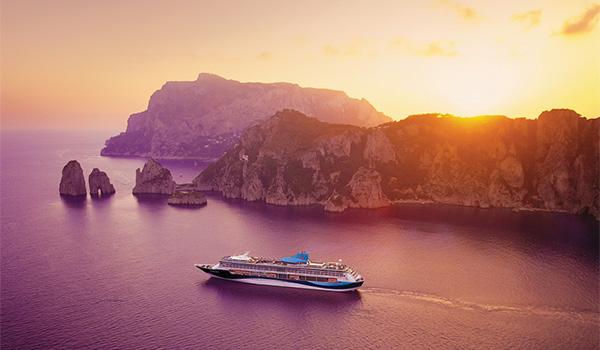 Navire de croisière au largue d'une île au coucher du soleil
