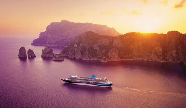 Cruise ship sailing past an island at sunset