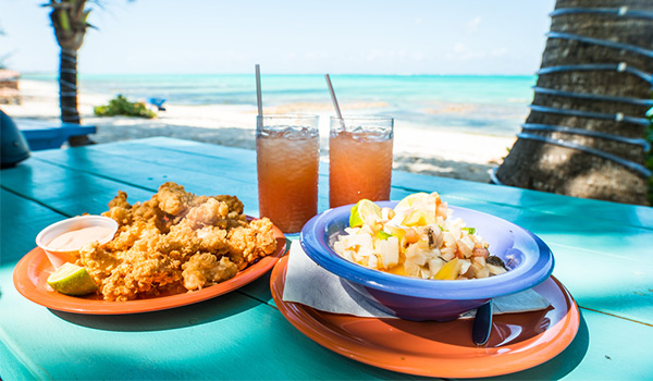 Conch fritters, conch salad and two punch drinks on a picnic table overlooking the beach