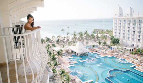 Bride standing on a balcony overlooking the pool and the ocean