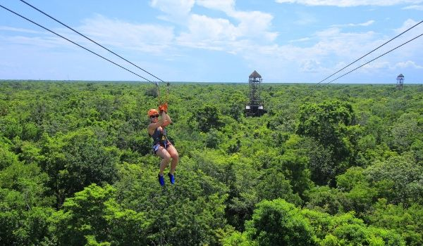Woman ziplining high above the rainforest canopy