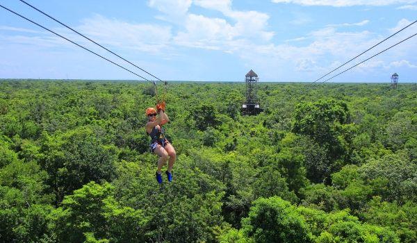 Woman ziplining high above the rainforest canopy