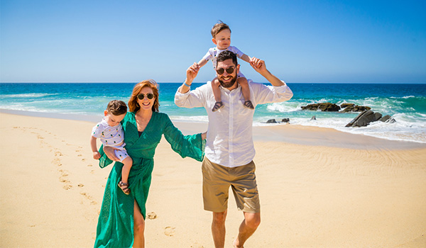 Mom, dad and two babies walking down a golden-sand beach with turquoise waters in the background