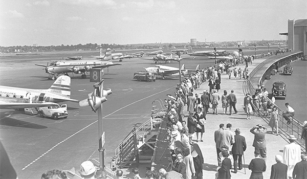 View from above of people walking along a tarmac lined with planes