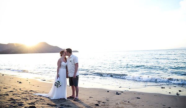 Bride and groom walking along the beach at sunset