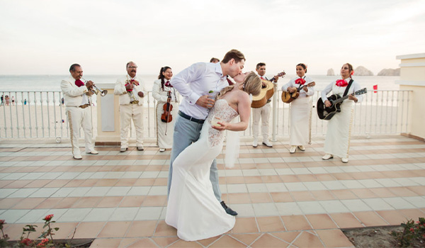Newlywed couple share a kiss in front of a mariachi band