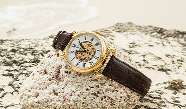 Wristwatch sitting on a rock on the beach