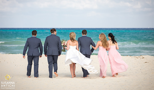 Groom and bride walking along the beach