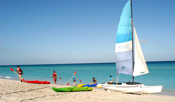 Vacationers on a pristine beach preparing to kayak through crystal-clear waters