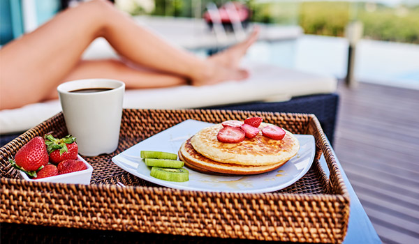 Pancakes, strawberries and a cup of coffee on a wicker tray next to a girl on a sun lounger