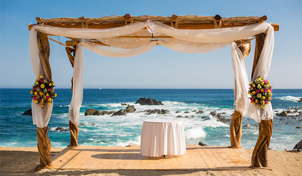 Rustic wedding altar draped in chiffon overlooking the ocean