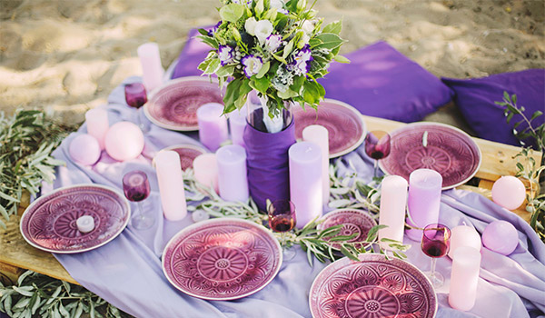 Table covered in purple plates, candles and flowers