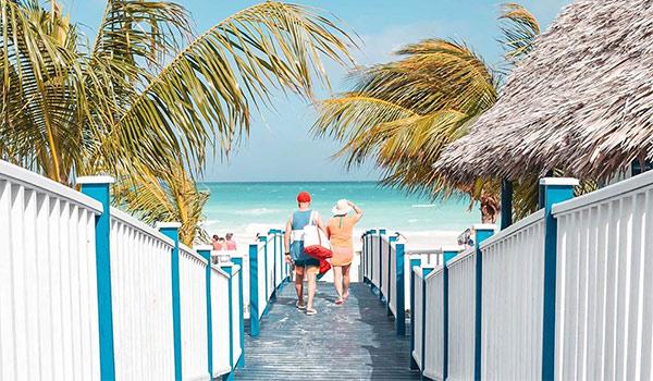 Man and woman walking along a boardwalk towards the beach