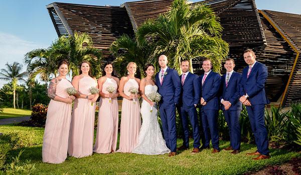 Bride, groom, bridesmaids and groomsmen posing in a lush garden