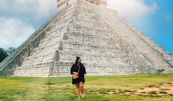 Woman standing in front of an ancient Mayan temple