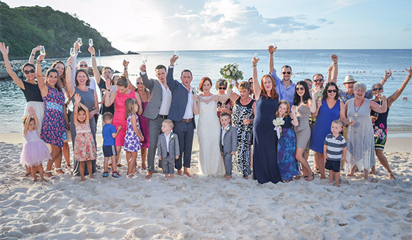 Couple posing with their guests on the beach
