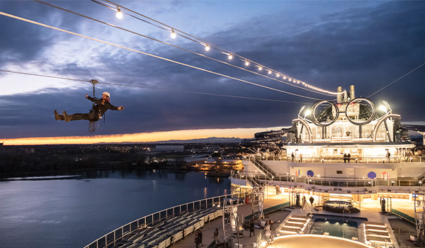 Person ziplining at night across the top of the cruise ship at night