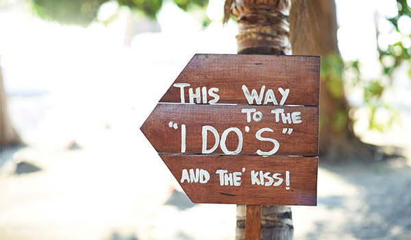 """Wooden sign on the beach saying """"I do"""""""