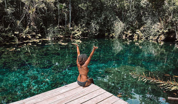 Woman sitting on a dock overlooking a cenote