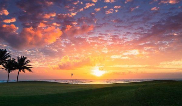 Collines verdoyantes du parcours de golf au coucher du soleil