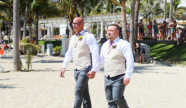 Groom and groom walking down the aisle on the beach