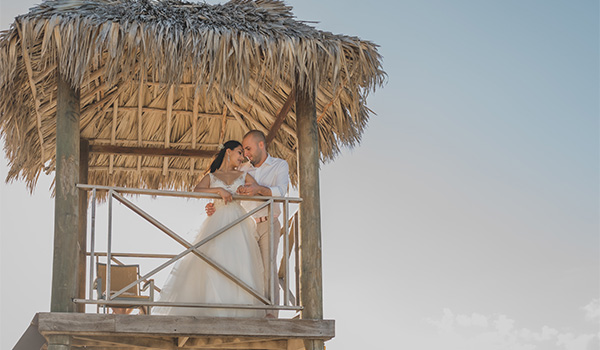 Bride and groom standing in a lifeguard hut on the beach