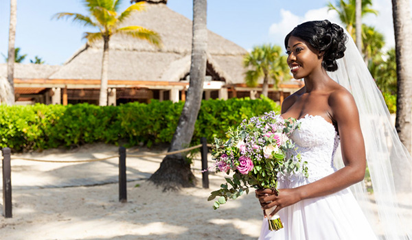 Bride in her wedding dress holding a tropical bouquet