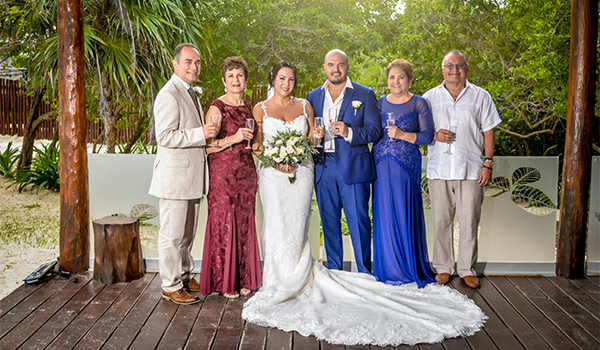 Bride and groom posing with their families on a deck