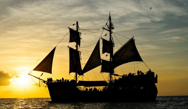 Pirate ship cruising across the water at sunset