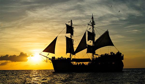 Navire de pirates voguant sur la mer au coucher de soleil