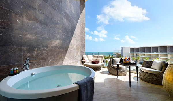 Jacuzzi on a sprawling balcony with several chairs overlooking the ocean