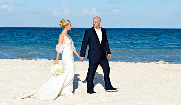 Groom and bride walking along the beach holding hands