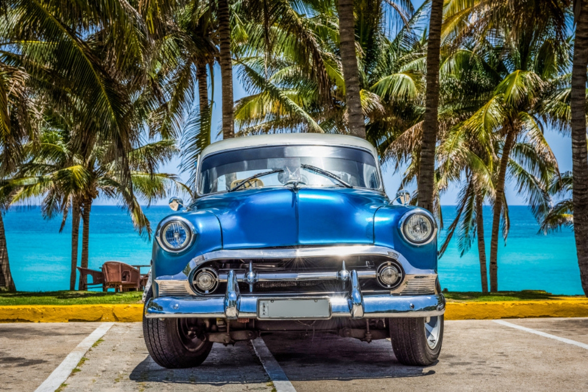Classic blue American car parked by the beach overlooking the blue water