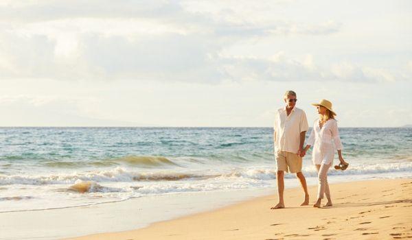 Un couple âgé se promenant sur la plage, main dans la main