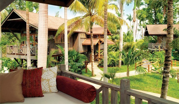 Furnished balcony overlooking treehouses in a lush garden