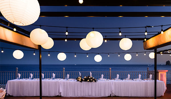 Wedding reception with fairy lights by the ocean